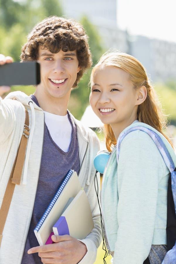 Amis masculins et féminins prenant le selfie avec le téléphone intelligent au campus d'université image libre de droits