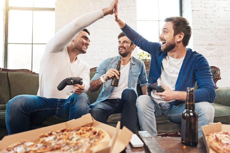 Amis masculins positifs donnant la haute cinq image stock