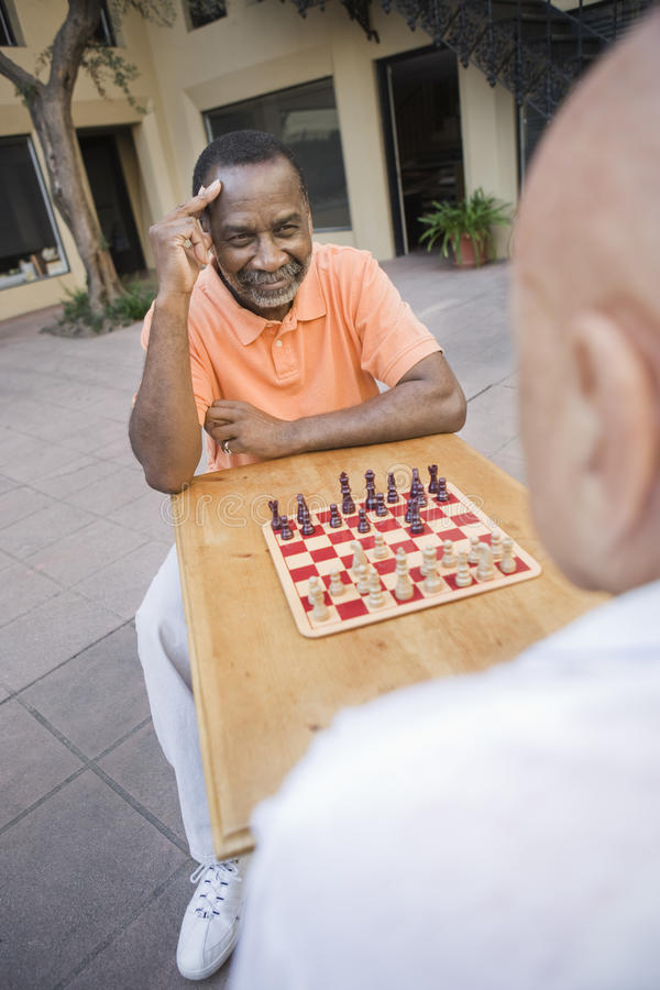 Amis masculins supérieurs jouant des échecs images libres de droits