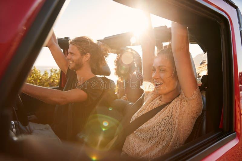 Amis millénaires enthousiastes des vacances de voyage par la route conduisant dans une voiture ouverte, fin, fusée de lentille photo stock