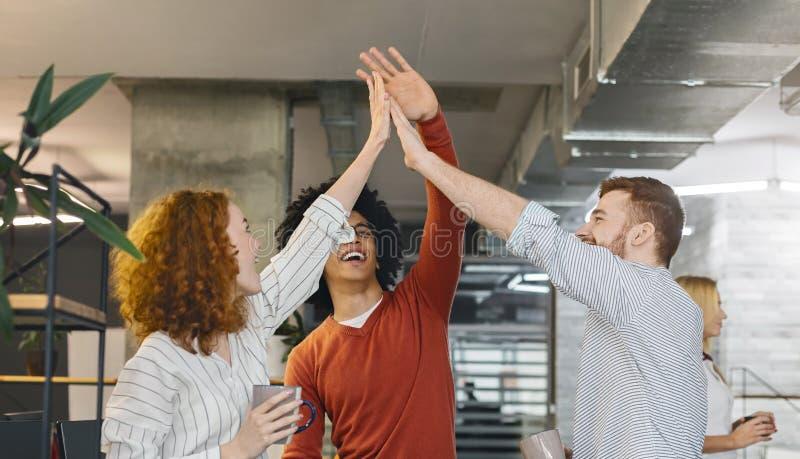 Amis millénaires multiraciaux donnant haut cinq dans le bureau photos libres de droits