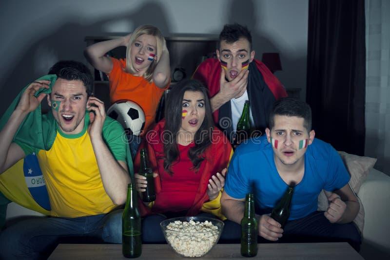 Amis observant la partie de football à la TV photographie stock