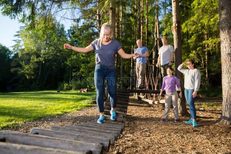 Amis observant le pont de rondin de croisement de femme dans la forêt image stock