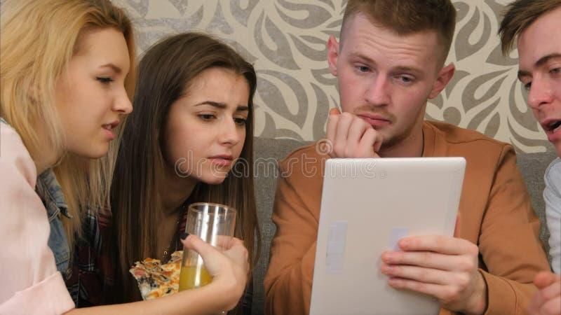 Amis observant le programm de comédie, utilisant le comprimé, et rire photographie stock