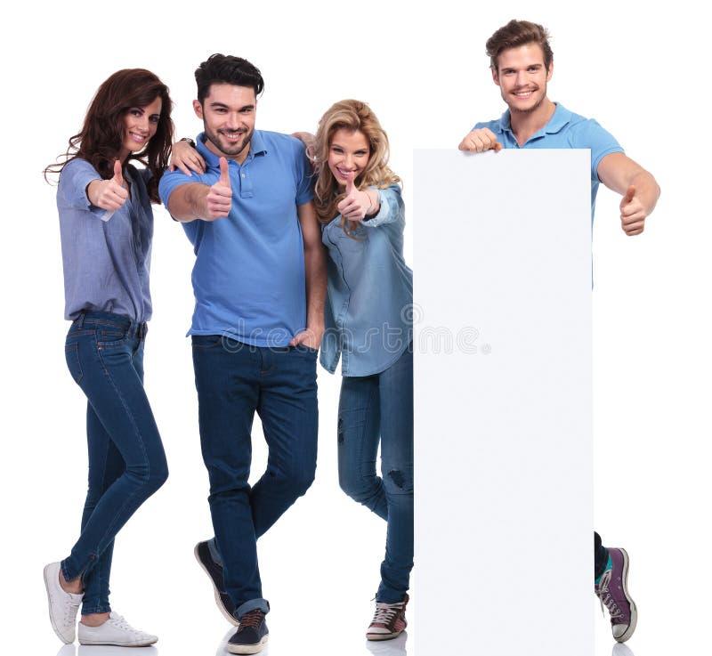 Amis occasionnels présent un conseil vide et faisant le signe correct photo stock