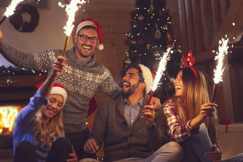 Amis ondulant avec des cierges magiques à la partie de nouvelle année photos stock