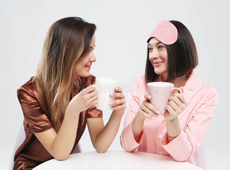 Amis ou adolescentes heureux avec le smartphone prenant le selfie et buvant du café au-dessus du fond blanc image libre de droits