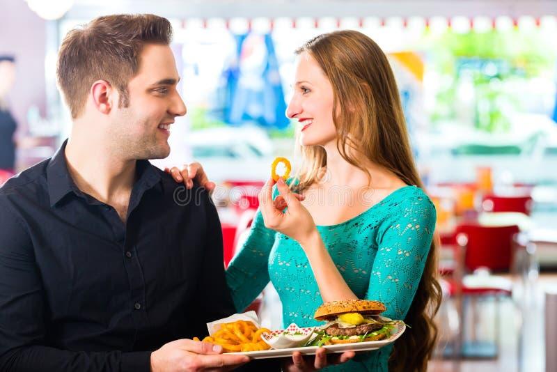 Amis ou couples mangeant des aliments de préparation rapide avec l'hamburger et les fritures image libre de droits