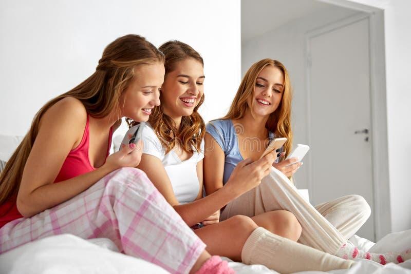 Amis ou filles d'ado avec des smartphones à la maison photo libre de droits