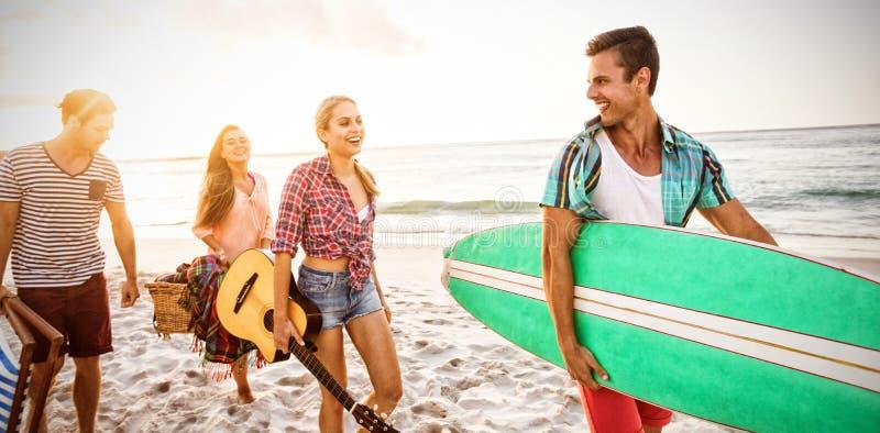 Amis portant une planche de surf et un panier illustration libre de droits