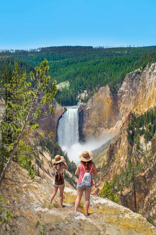 Amis prenant des photos et appréciant la belle vue de la cascade sur augmenter le voyage dans les montagnes image stock