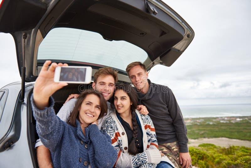 Amis prenant le selfie tandis que sur une promenade en voiture le long de la côte photographie stock libre de droits