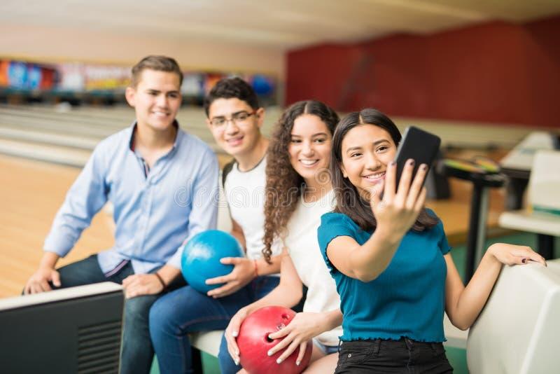 Amis prenant Selfie au téléphone portable dans le club de bowling image libre de droits