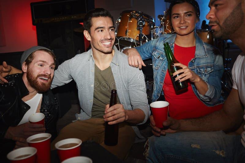 Amis refroidissant avec de la bière à la partie image libre de droits