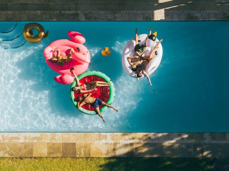 Amis refroidissant sur des matelas d'air dans la piscine photo stock