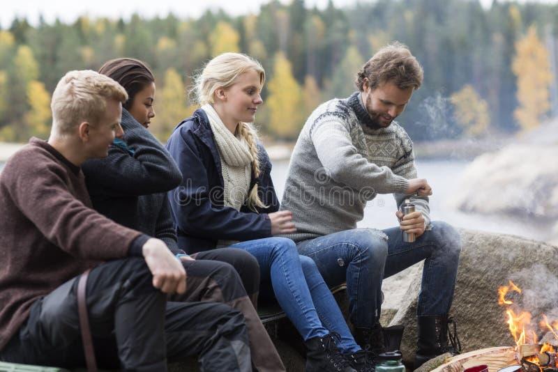 Amis regardant le café de meulage de l'homme le terrain de camping photo stock