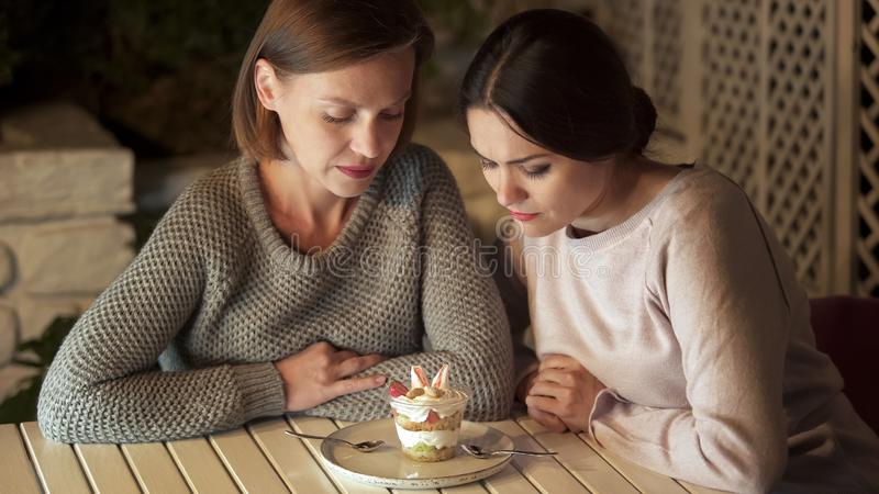 Amis regardant le dessert crémeux voulant le manger, suivant un régime, nutrition saine photos libres de droits