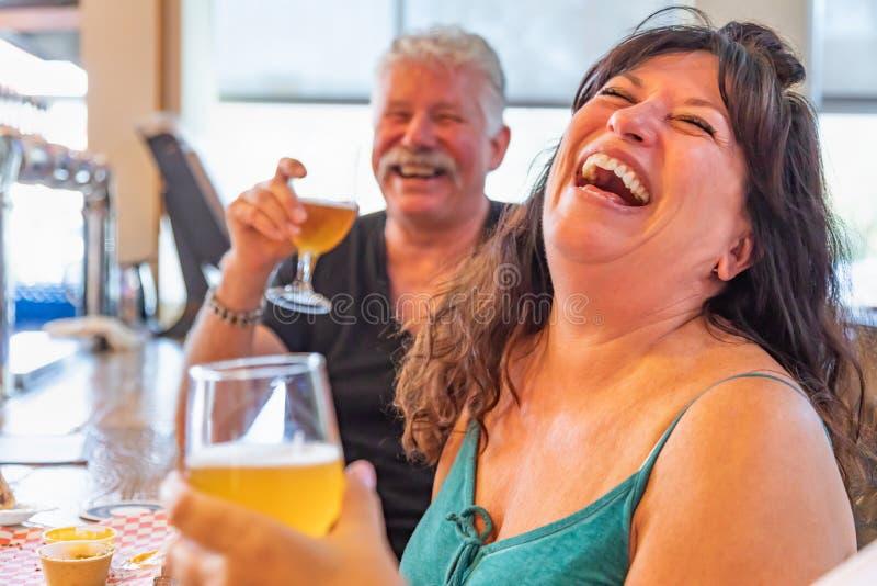 Amis riants appréciant des verres de bière micro de brew à la barre photographie stock