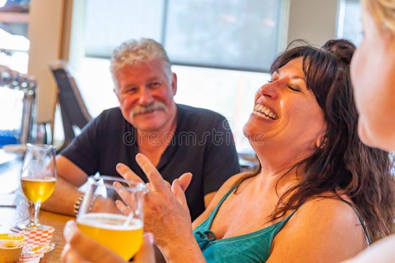 Amis riants appréciant des verres de bière micro de brew à la barre image libre de droits