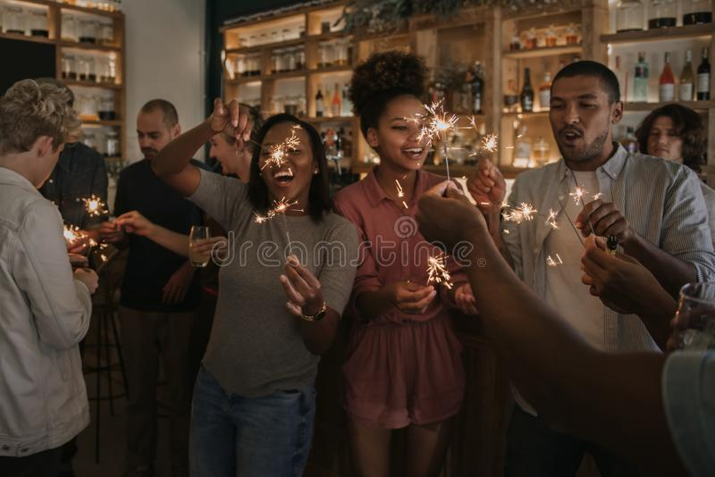 Amis riants célébrant avec des cierges magiques dans une barre la nuit photographie stock libre de droits