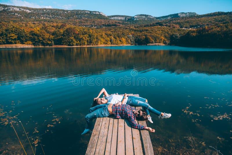 Amis s'asseyant sur le pair par le lac image stock