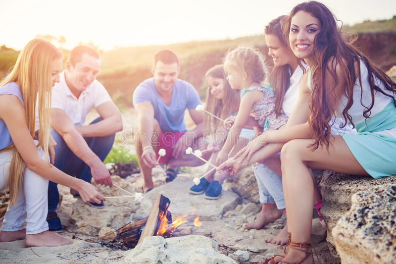 Amis s'asseyant sur le sable à la plage en cercle images stock