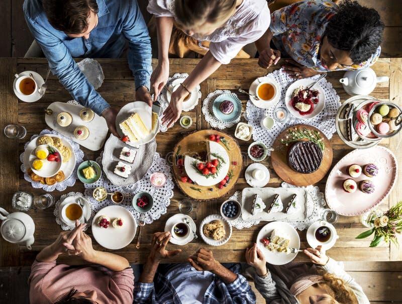 Amis se réunissant ensemble sur le plaisir h de gâteaux de consommation de thé images libres de droits
