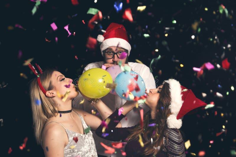 Amis soufflant des ballons à la partie du ` s de nouvelle année photographie stock libre de droits