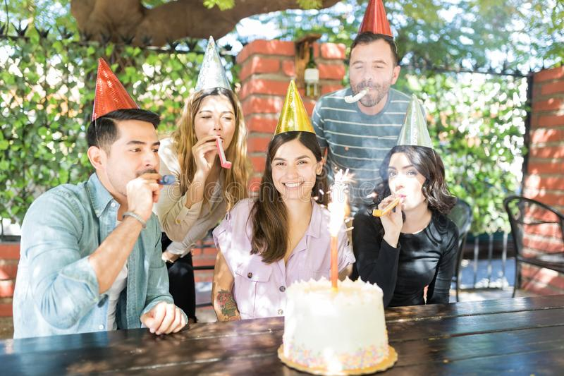 Amis soufflant des klaxons de partie sur l'anniversaire de la femme photo stock