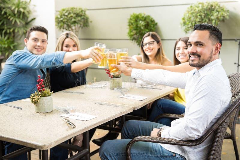 Amis soulevant leurs verres pour un pain grillé photos stock