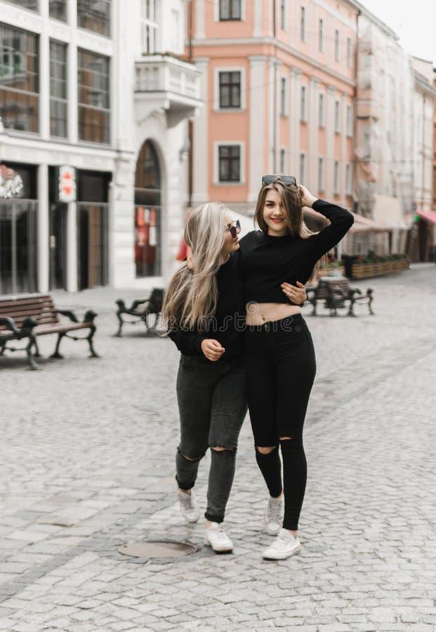 Amis souriant et marchant dans la vieille ville photographie stock