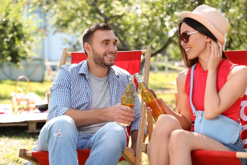 Amis souriants qui mettent des bouteilles à pique-nique pendant la journée d'été images stock