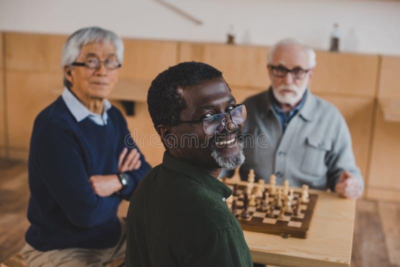 Amis supérieurs jouant des échecs photographie stock libre de droits