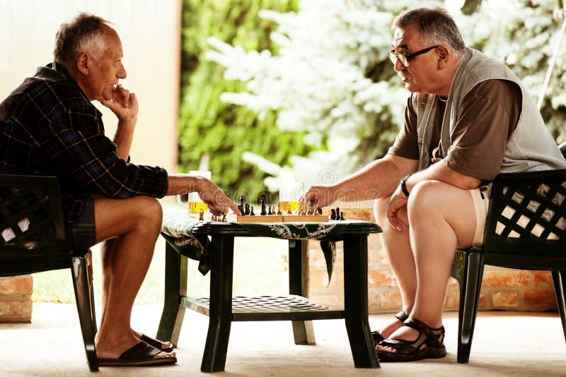 Amis supérieurs jouant des échecs image libre de droits