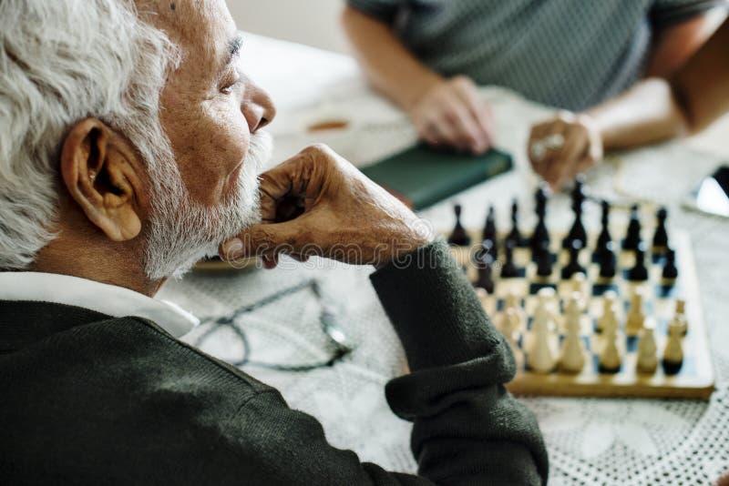 Amis supérieurs jouant des échecs ensemble images stock