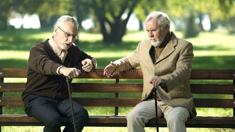 Amis supérieurs parlant et riant, se reposant sur le banc en parc, souvenirs heureux images stock