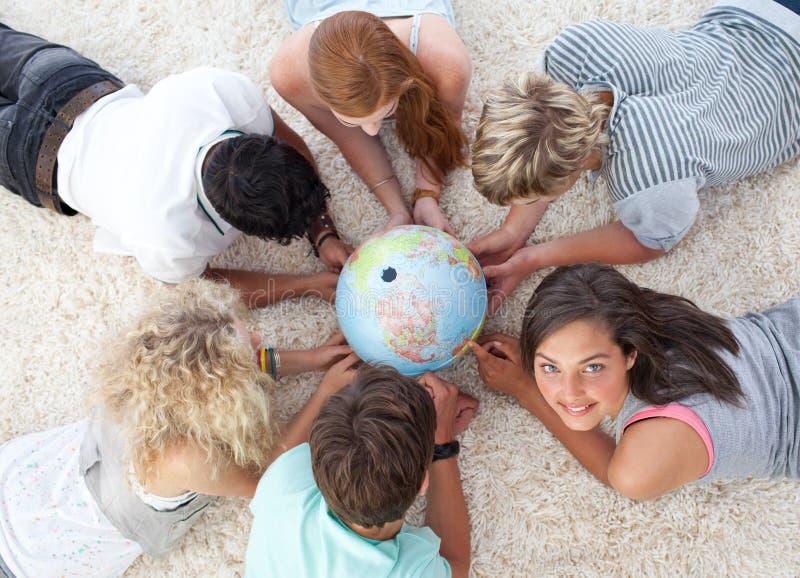 Amis sur l'étage examinant un monde terrestre photographie stock libre de droits
