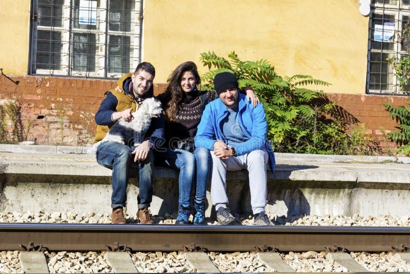 Amis sur la station de train attendant le train photographie stock libre de droits