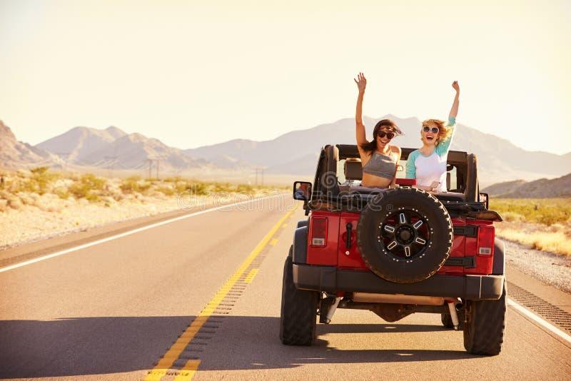 Amis sur le voyage par la route conduisant dans la voiture convertible image libre de droits