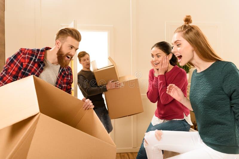 Amis tenant des boîtes en carton à la nouvelle maison photo libre de droits