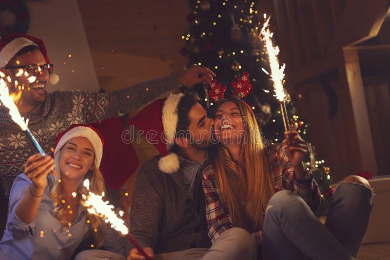 Amis tenant des cierges magiques pour le ` s Ève de nouvelle année photo stock
