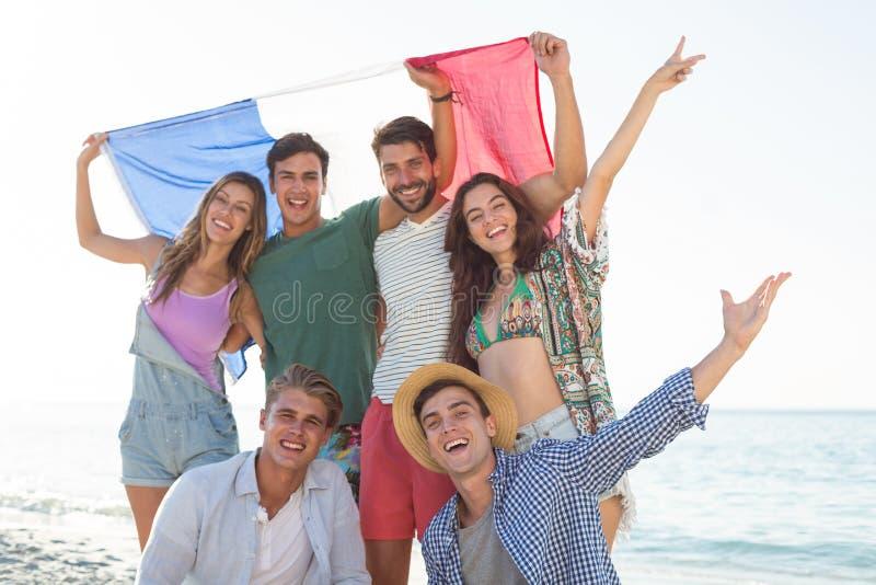 Amis tenant le drapeau français sur le rivage à la plage photo libre de droits
