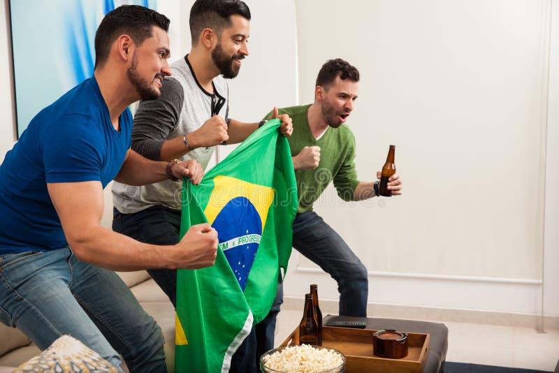 Amis tenant un drapeau brésilien photographie stock libre de droits