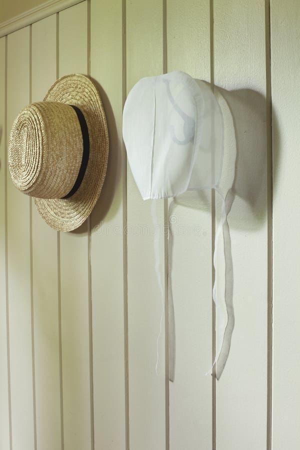 Amische Mütze und Strohhut, die an der Wand hängt stockfotografie