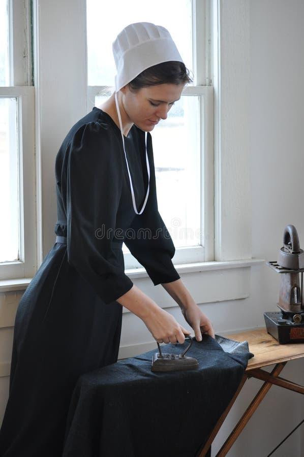 Amisches junge Frauen-Bügeln lizenzfreies stockfoto