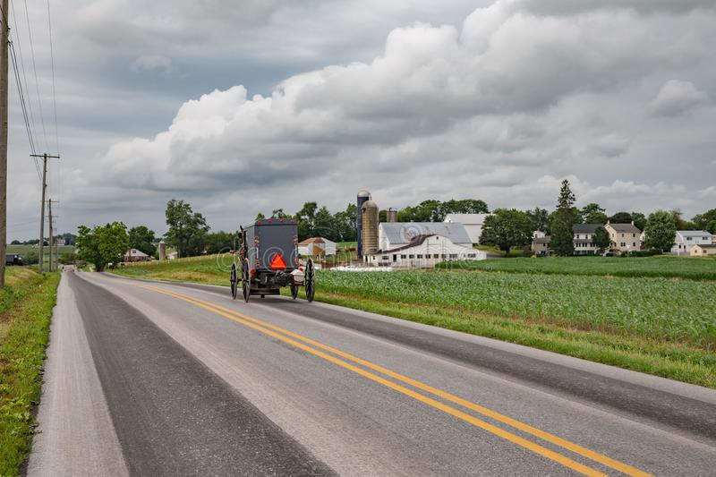 Amish Buggy on a Country Road. Rear view of Amish buggy going down a country road in Lancaster County, PA stock photos