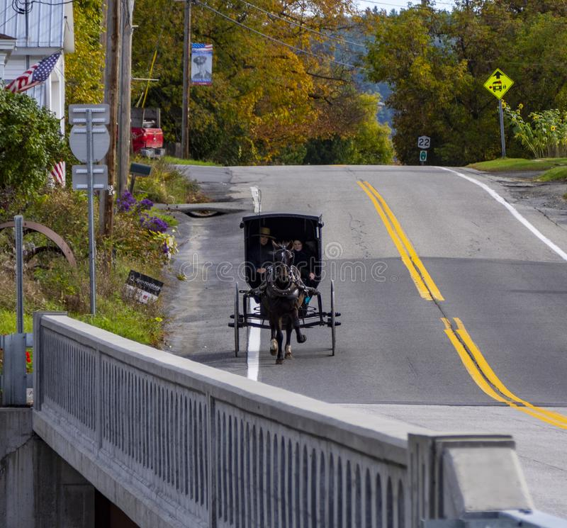 An Amish Carriage rides through Upper New York State. An Amish couple riding through a small New York State community in a small black carriage pulled by a horse stock photography