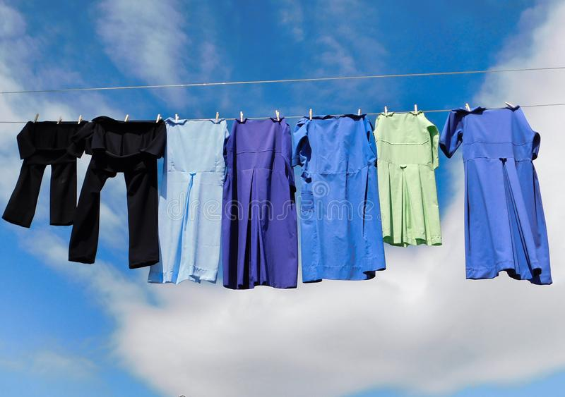 Amish clothing line drying. Handmade Amish dresses and black pants drying on a clothing line in the breeze, with blue skies and clouds in the background stock photography