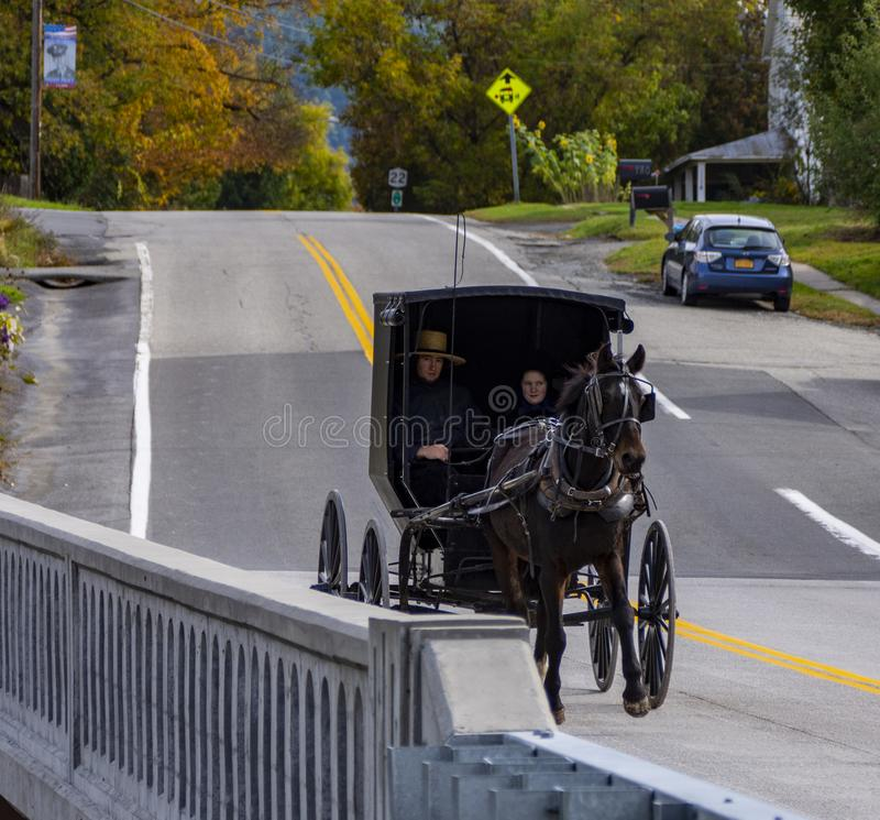 Black Horse pulls an Amish Carriage in Upper New York State during Autumn. An Amish couple riding through a small town in Upper New York State during the New stock photography