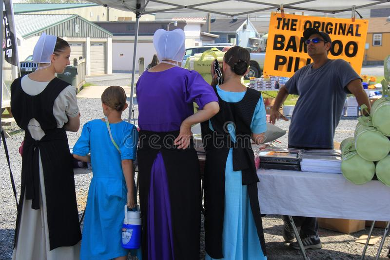 Amish family standing at table inspecting goods they might want to buy, Green Dragon Farmers Market, Ephrata, PA, 2016 stock photography